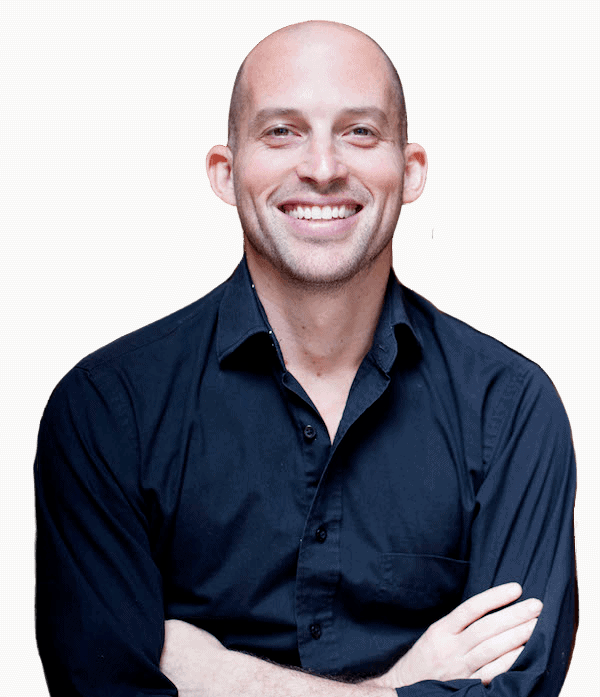Portrait photo of Matt Landau. He's wearing a dark blue dress shirt. He has a big smile and his arms are crossed.
